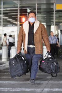 An AeroMexico Flight 408 passenger Sixto Zamora, who flew on from Mexico City to JFK Airport in Jamaica, New York, wears a protective mask as the number of cases of people infected with Swine Flu increase on Monday, April 27, 2009. (Charles Eckert/Newsday/MCT)