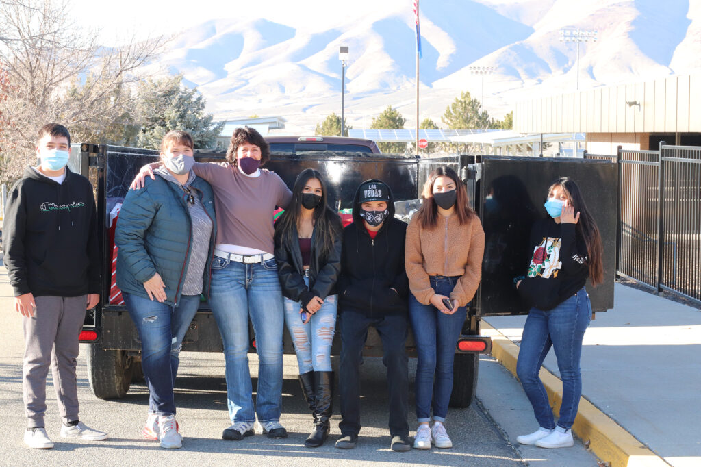 Representatives from FCAA, Mrs. Alexis Mattson and students stand in front of a trailer loaded with presents./Kiley Dayton • Lowry Multimedia Communication