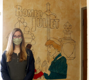 Madisyn Andrade standing in front of her Romeo and Juliet mural in the English hallway. /Alexis Galarza • The Brand