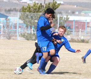 Nazareth Razo and Avery Wirthlin collide with a Fernley player. /Ron Espinola • The Brand