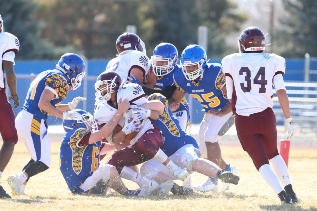 The Elko running back is brought down a group of Lowry tacklers. /Ron Espinola • The Brand