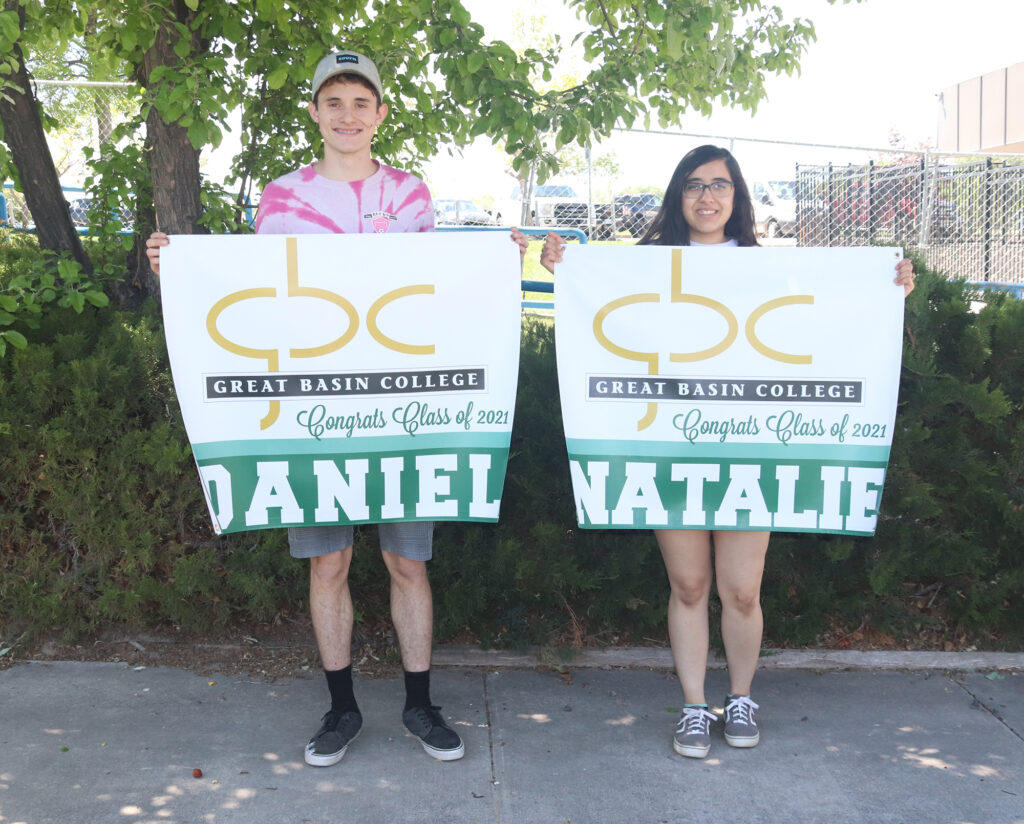 Natalie Contreas and Daniel Fernandez holding graduation signs from GBC. /Ron Espinola • The Brand