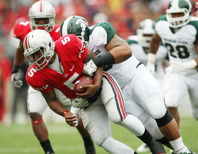 Ohio State QB Braxton Miller (5) is sacked by Michigan State defensive tackle Jerel Worthy (99). /Neal C. Lauron • Columbus Dispatch/MCT