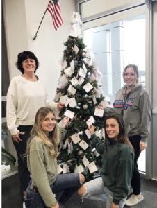 Junior class advisor Alexis Mattson with junior class officers Lauren Fentress, Anjolie Karrer, and Téa Novi posing in front of the Angel Tree./Araceli Galarza • The Brand