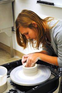 Art Club member Kristi Ingle demonstrates wheel-throwing a bowl. /Courtesy • Courtney Rorex